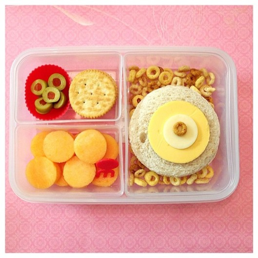 It's a Circle Thing ⭕️ sandwich with cheeses on top, Cheerios, cantaloupe, Ritz crackers, and cut-up green olives.