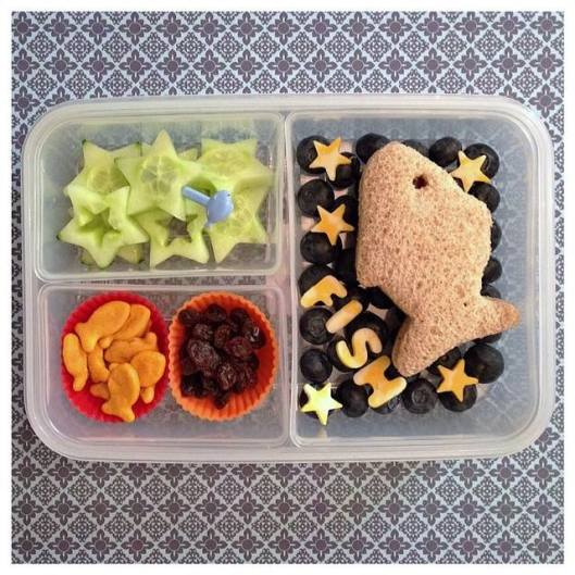 "A fish-shaped sandwich on a ""sea"" of blueberries with cheese stars, cucumbers, goldfish crackers, and some raisins."