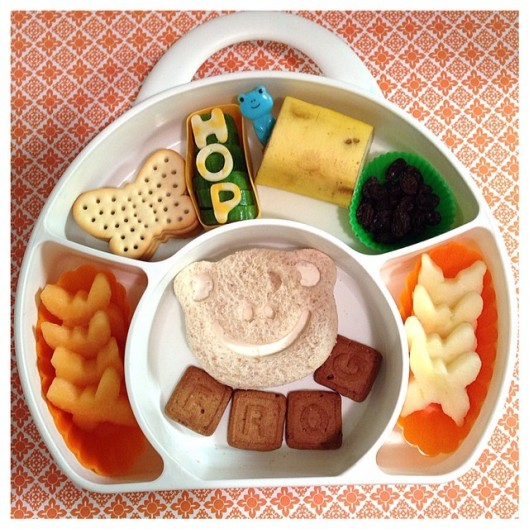 "Frog-face shaped sandwich, letter cookies spelling the word ""frog"", butterfly-shaped apples and cantaloupes, butter crackers, cucumbers w/ cheese on top spelling the word ""HOP"", a piece of banana with a frog pick, and some organic raisins!"