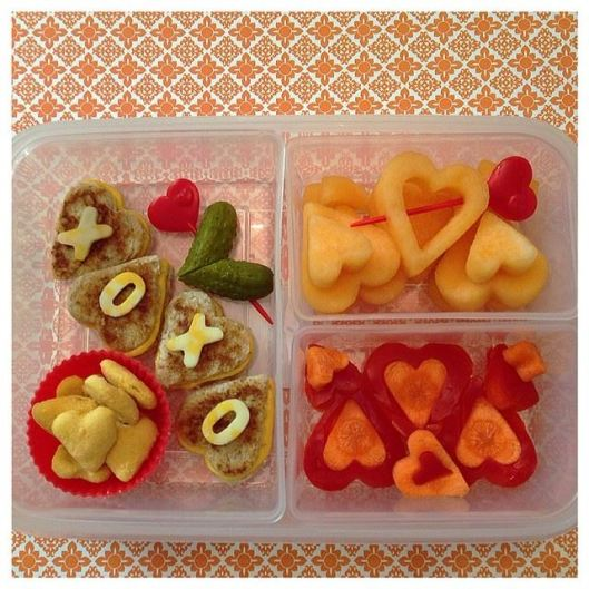 Grilled cheese sandwiches (heart-shaped), heart-shaped cheese crackers, heart-shaped pickle, cantaloupe, carrots with red peppers.