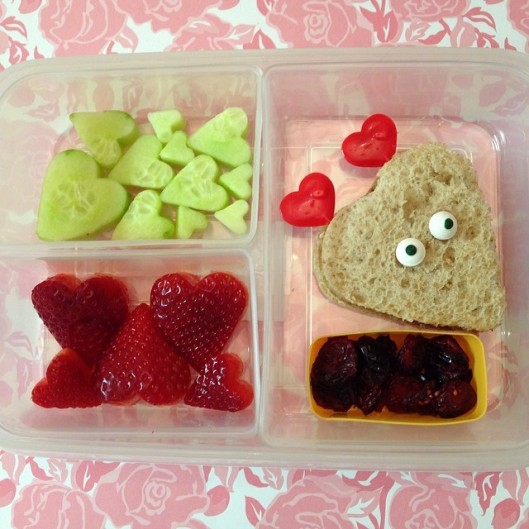 Strawberries, cucumbers, soy butter and jelly sandwich, and some dry cranberries.