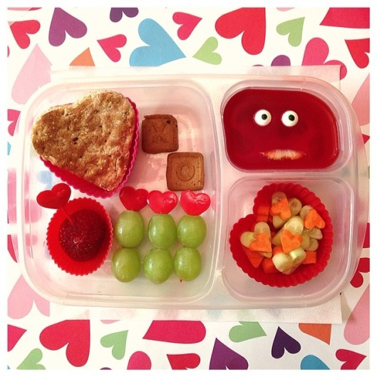 Heart-shaped sandwich, a strawberry, grapes, strawberry jello, and some cucumbers and carrots mixed together