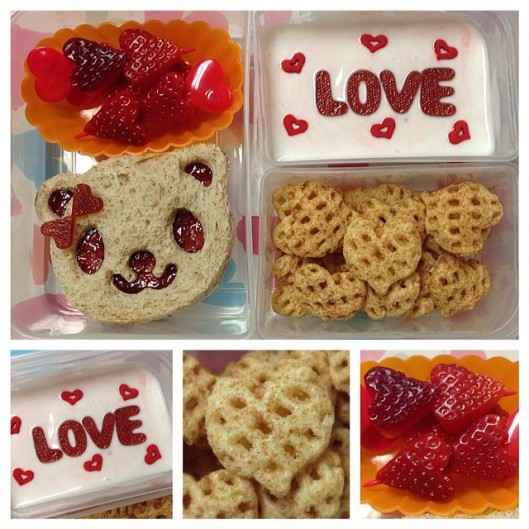 Jelly sandwich w/ a bit of cream cheese, heart-shaped strawberries, heart-shaped cinnamon cereal, yogurt with heart sprinkles and the word LOVE made from fruit leather.