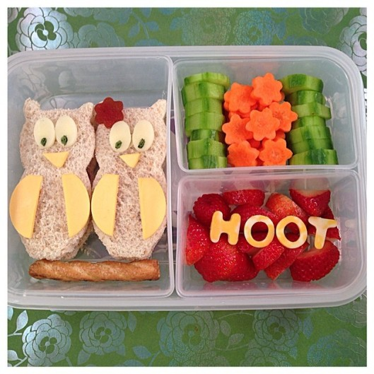 Owl-shaped sandwiches sitting on a pretzel, cucumbers and carrots, and strawberries with cheese!