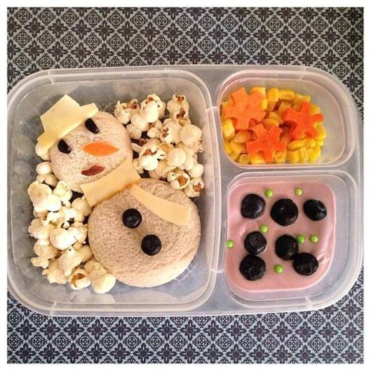 Cream cheese and jelly snowman sandwich, with popcorn (snow), corn and snowflake-shaped carrots, and blueberry yogurt with blueberries and some sprinkles.