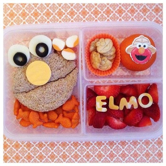 Elmo cream cheese sandwich (eyes: mozzarella cheese & black eyes, nose: American cheese), Goldfish crackers (for Elmo's pet fish, Dorothy), organic Elmo crackers, a clementine with an Elmo sticker, strawberries, and ELMO made from coby-jack cheese.