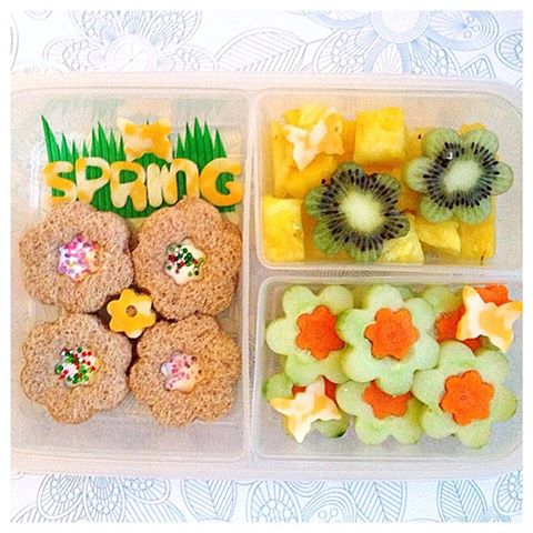 4 mini flower-shaped cream cheese sandwiches, cucumbers with mini carrots in the middle, pineapples with flower-shaped kiwis, and coby jack cheese to spell SPRING and to make the butterflies.