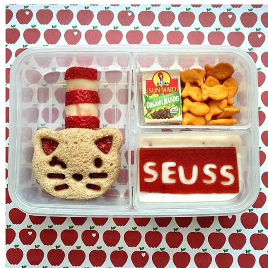 The Cat in the Hat, by Dr. Seuss: Cat-shaped sandwich, strawberries and apples as the hat, yogurt with fruit leather spelling SEUSS, goldfish, and raisins.