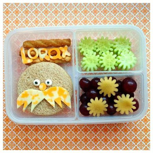 "The Lorax by Dr. Seuss: Lorax sandwich, pretzels with cheese, cucumber ""tree tops"", grapes with plum ""tree tops""."